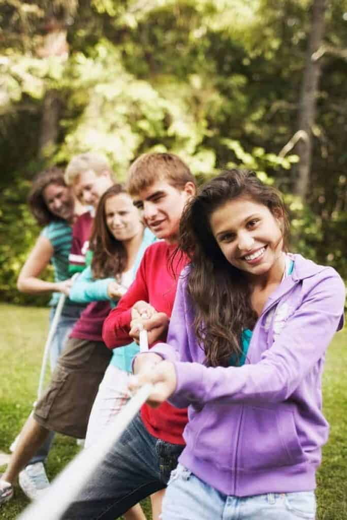 Teenagers playing a game of tug of war in a grassy field.