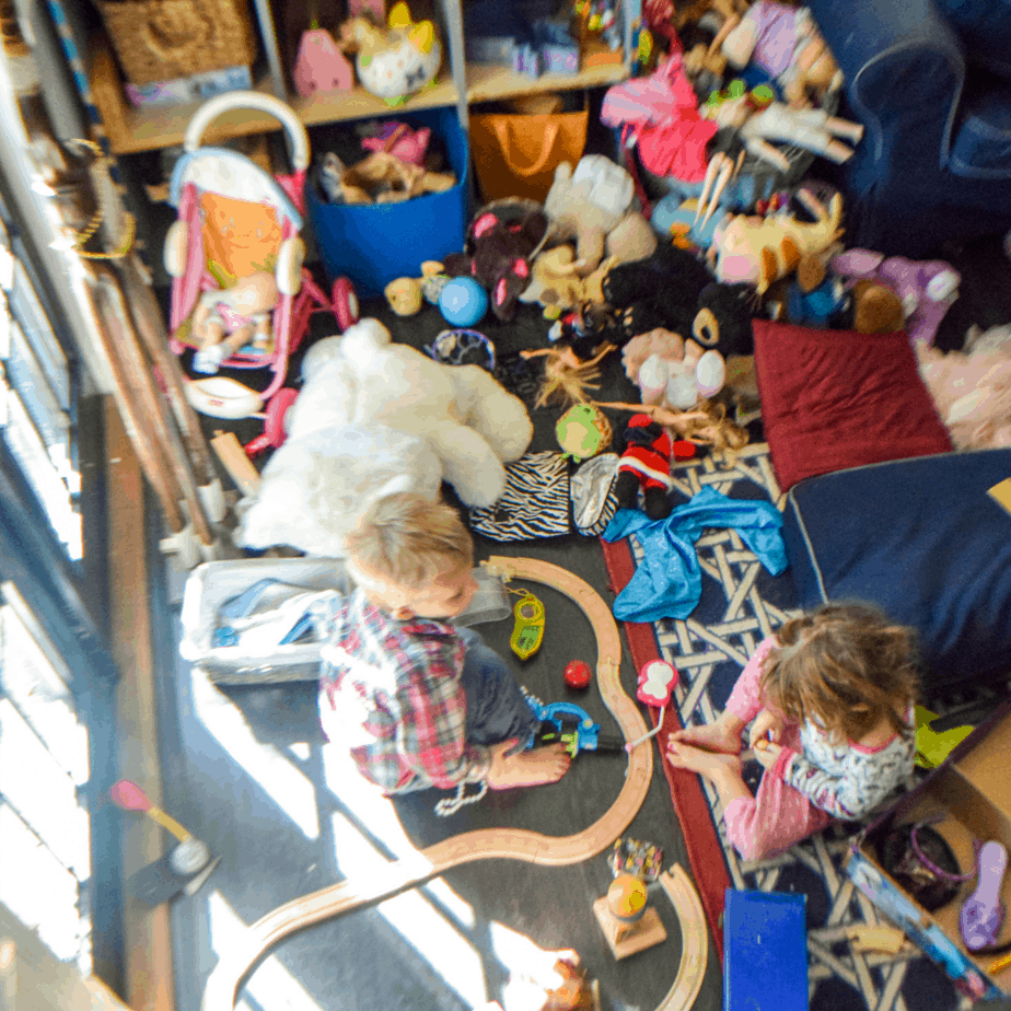 Two toddlers trying to play in a very messy play space that is so covered with toys that you can barely see the floor